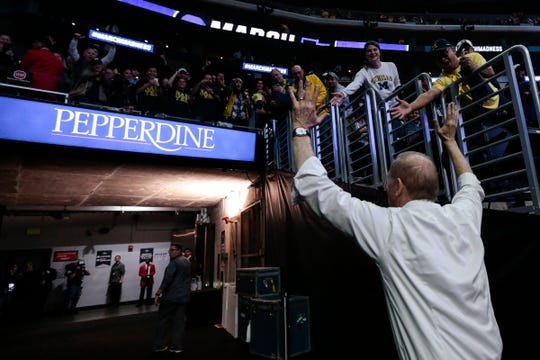 Michigan head coach John Beilein high fives fans as he walks off the court after defeating Texas A&M at Sweet 16 of the NCAA tournament at Staples Center in Los Angeles, Calif., Thursday, March 22, 2018.
