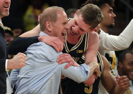 Michigan head coach John Beilein, left, celebrates with Michigan forward Moritz Wagner (13) after Michigan defeated Purdue 75-66 to win the NCAA Big Ten Conference tournament championship college basketball game, Sunday, March 4, 2018, in New York.
