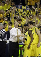 Michigan head coach John Beilein talks to Kelvin Grady, center, and Zack Novak as they plan strategy in the last minute of their win over Duke in Ann Arbor, MI on Saturday, December 6, 2008.Bottom is Duke's Lance Thomas. Michigan went on to a 81-73 upset win over Duke.