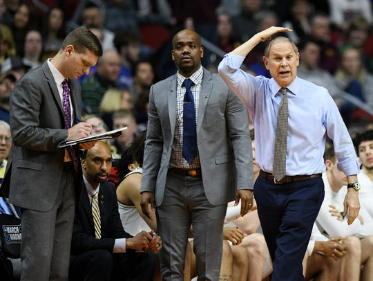 Michigan head coach John Beilein, right, calls a play next to assistant coaches Luke Yaklich, left, and DeAndre Haynes during an NCAA Tournament game.