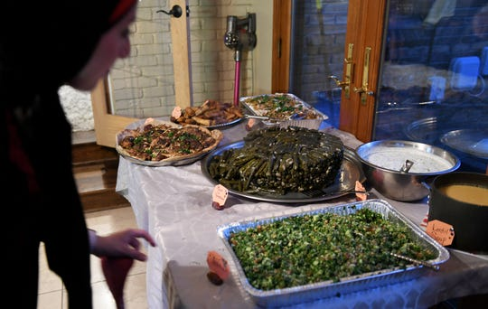 Ameena Elder, 34, lays out a spread of grape leaves, tabouli, lentil soup, cucumber salad, musakhan and sambusa for her family and extended family at her home in Dearborn on May 23, 2018.