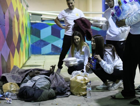 Helping Handzzz founder Nadine Daoud, 22, of Dearborn, right, asks a man what kind of chips he would like while she, President Sarah Esseily, 22, left, of Canton and others from Helping Handzzz give food to presumably homeless people at Hart Plaza in Detroit late Friday.