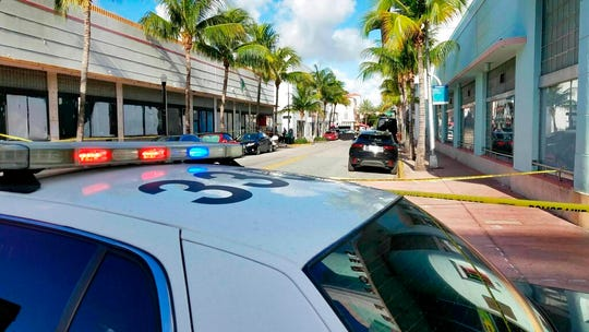 In this Saturday, May 11, 2019 photo, Miami Beach police investigators gather evidence on EspaAola Way between Collins and Washington after an early morning shooting.