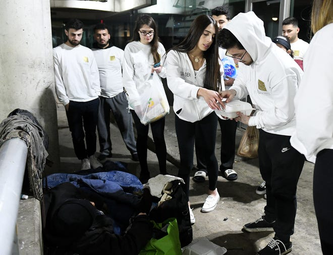 Helping Handzzz founder Nadine Daoud, 22, of Dearborn, center, and Daoud Wehbi, 21, of Dearborn Heights, right, check the food that they and others from Helping Handzzz are giving to a presumably homeless man at Hart Plaza in Detroit on Friday.