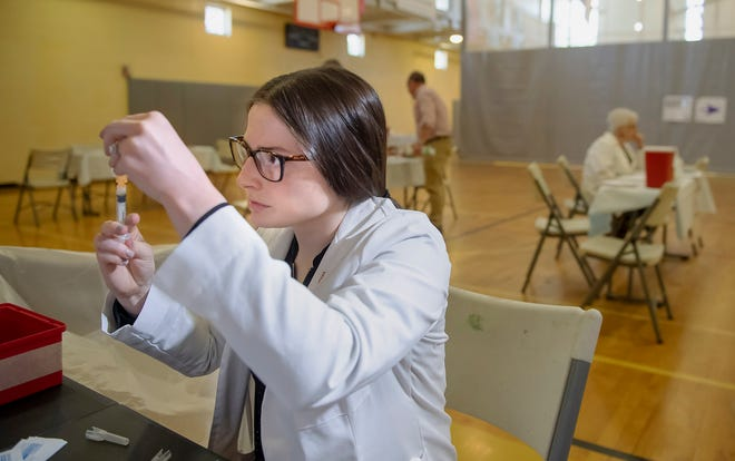University of Pittsburgh pharmacy student Alexandria Taylor prepares syringes during a free measles vaccination clinic by the Allegheny County Health Department at the Homewood-Brushton YMCA in Pittsburgh.