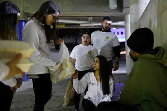 Helping Handzzz founder Nadine Daoud, 22, of Dearborn, lower right, and Irena Zapotny, 17, left, of Dearborn Heights and others from Helping Handzzz give food to Gregory Winans, 35, right, at Hart Plaza in Detroit late Friday night. Standing behind Nadine is Alayna Berri, 11, of Dearborn Heights and Ali Abdallah, 23, of Dearborn.