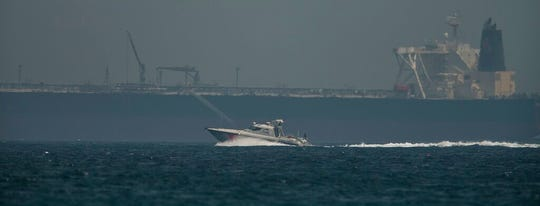 "An Emirati coast guard vessel passes an oil tanker off the coast of Fujairah, United Arab Emirates, Monday, May 13, 2019. Saudi Arabia said Monday two of its oil tankers were sabotaged off the coast of the United Arab Emirates near Fujairah in attacks that caused ""significant damage"" to the vessels, one of them as it was en route to pick up Saudi oil to take to the United States."