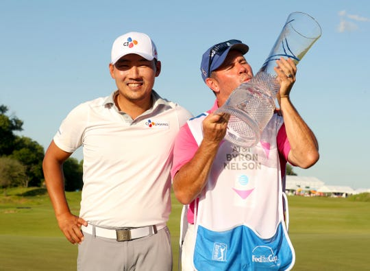Sung Kang, winner of the Byron Nelson golf tournament, poses for a photo with his caddy Jason Shortall, who kisses the trophy.