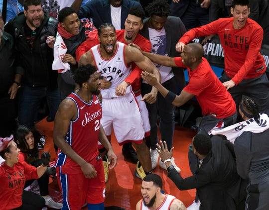 Toronto Raptors forward Kawhi Leonard, center, reacts with teammates after making the winning shot as Philadelphia 76ers center Joel Embiid (21) walks away at the end of the game.