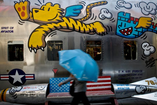 A woman walks by a bench painted with an American flag outside a fashion boutique selling U.S. brand clothing at the capital city's popular shopping mall in Beijing, Monday, May 13, 2019.