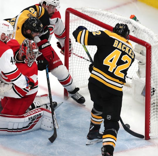 Carolina Hurricanes goaltender Petr Mrazek, second from left, looks back as Boston Bruins' David Backes (42) pokes the puck in for a goal during the third period.