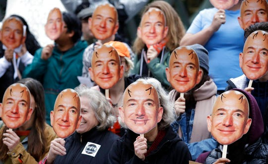 """In this Oct. 31, 2018, file photo, demonstrators hold images of Amazon CEO Jeff Bezos near their faces during a Halloween-themed protest at Amazon headquarters over the company's facial recognition system, """"Rekognition,"""" in Seattle. San Francisco is on track to become the first U.S. city to ban the use of facial recognition by police and other city agencies as the technology creeps increasingly into daily life."""