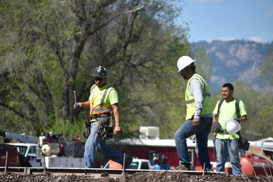 A construction crew lays forms Monday morning for the concrete sidewalk being installed along North College Avenue.