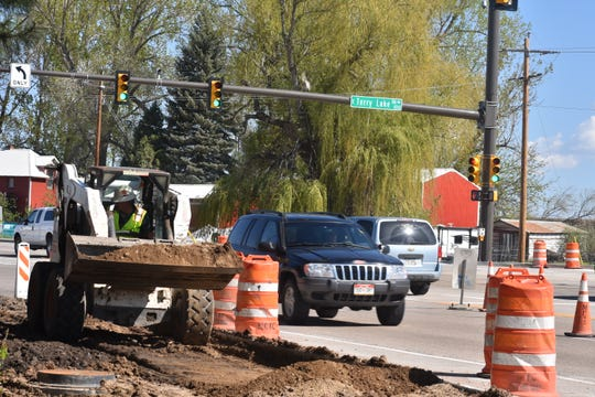 A construction worker brings soil to where a sidewalk will be built along North College Avenue just south of Colorado Highway 1 on Monday.