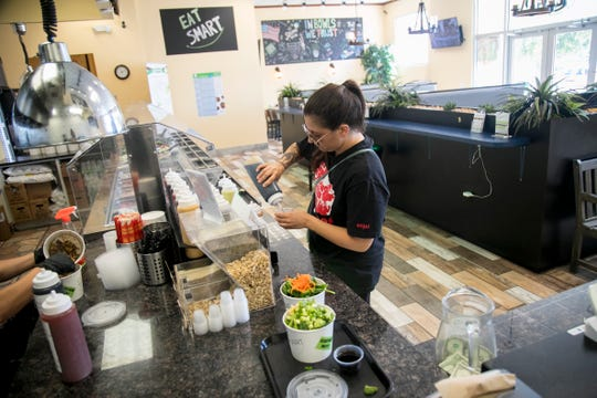 Brittany Gray selects her sauce to top her vegan bowls that she created at Eat Smart in Cape Coral on Friday, May 10, 2019. Eat Smart has tofu as well as meat and seafood to add to the bowls.