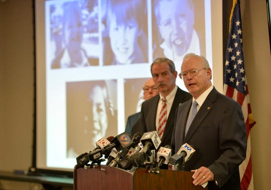 Sheriff McCarty, flanked by FBI agent Dave Thomas, addresses the media, as photos of Timothy Ray Jones Jr. children are on display, during a news conference at the Lexington County Sheriff's Dept Training Center in Lexington, S.C., Wednesday, Sept. 10, 2014.  Jones Jr., 32, will be charged with murder in the deaths of his five children after he led authorities to a secluded clearing in Alabama, where their bodies were found wrapped in garbage bags, McCarty said Wednesday.  (AP Photo/ Richard Shiro)