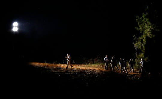 A group of investigators gather under a light near the crime scene on Tuesday, Sept. 9, 2014, in Camden, Ala. Wilcox County, Alabama, District Attorney Michael Jackson told The Associated Press that Timothy Ray Jones Jr. is suspected of killing his children in South Carolina and leaving their bodies in a rural area near Camden. (AP Photo/Brynn Anderson)