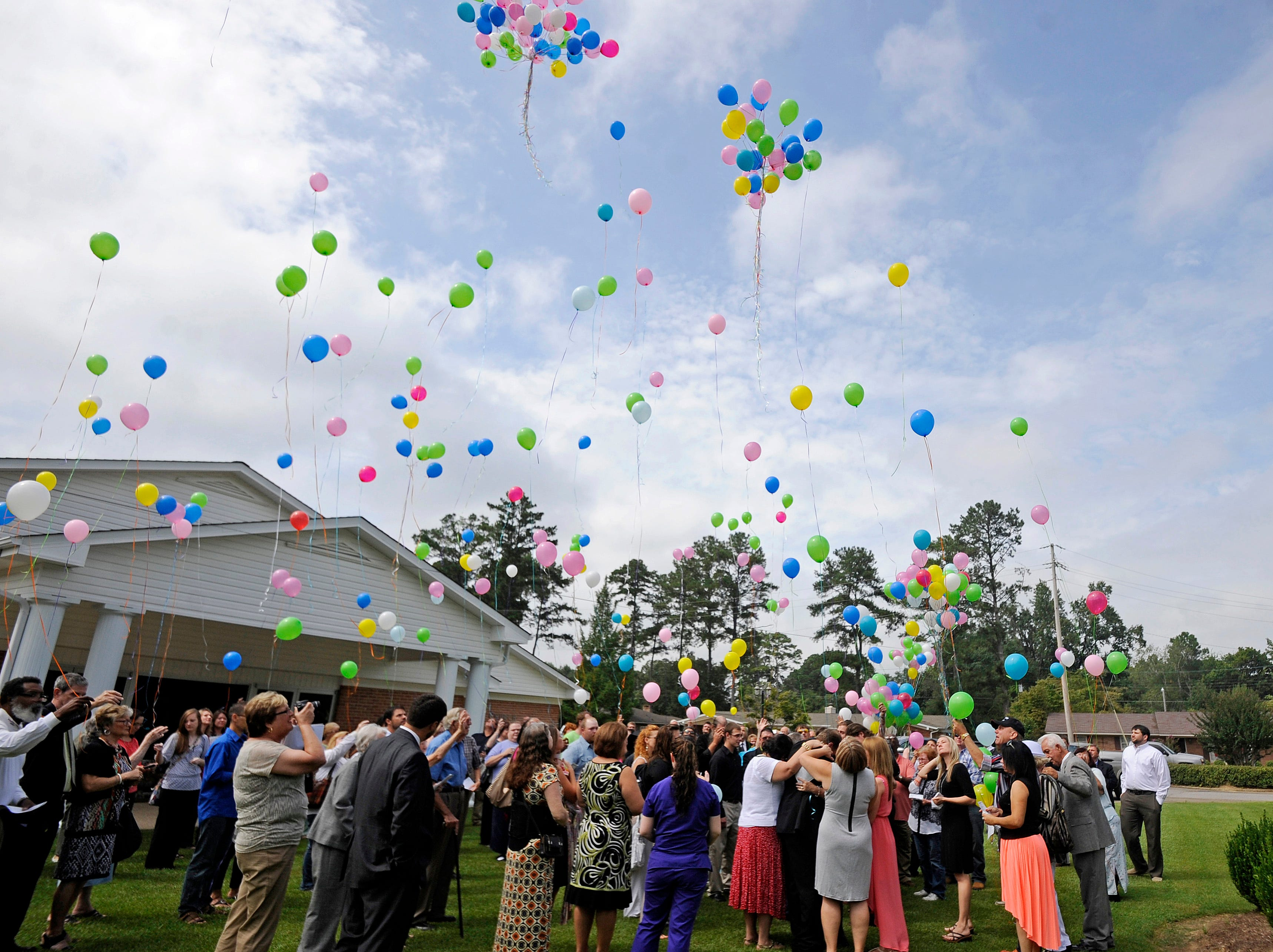 Mourners release balloons at the end of a memorial service in Amory, Miss., Friday, Sept. 12, 2014.  Police say Timothy Ray Jones Jr., 32, killed his three boys and two girls, wrapped their bodies in separate trash bags and drove around for days across several states with their decomposing bodies before dumping them on a rural hilltop in Alabama. The children were remembered at the Amory Church of Christ. A program showed a photo of each child smiling and offered a description of what they liked to do.  (AP Photo/Thomas Graning)