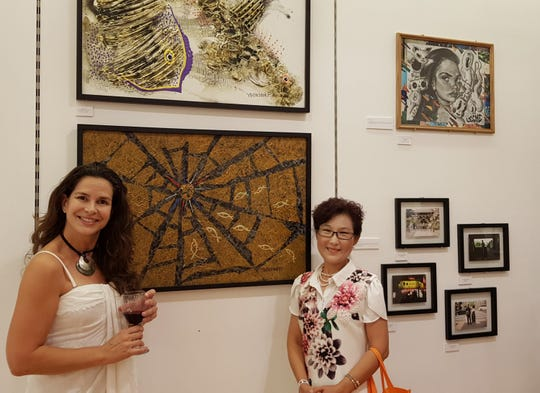 "Local artist Yeon Sook Park displays her  art at the GAX (Guam Art Exhibit) ""Pow! Wow!"" art of Guam at The Plaza Shopping Center, second floor, Tumon. Pictured on April 6 is Donna Baker and Yeon Sook Park."