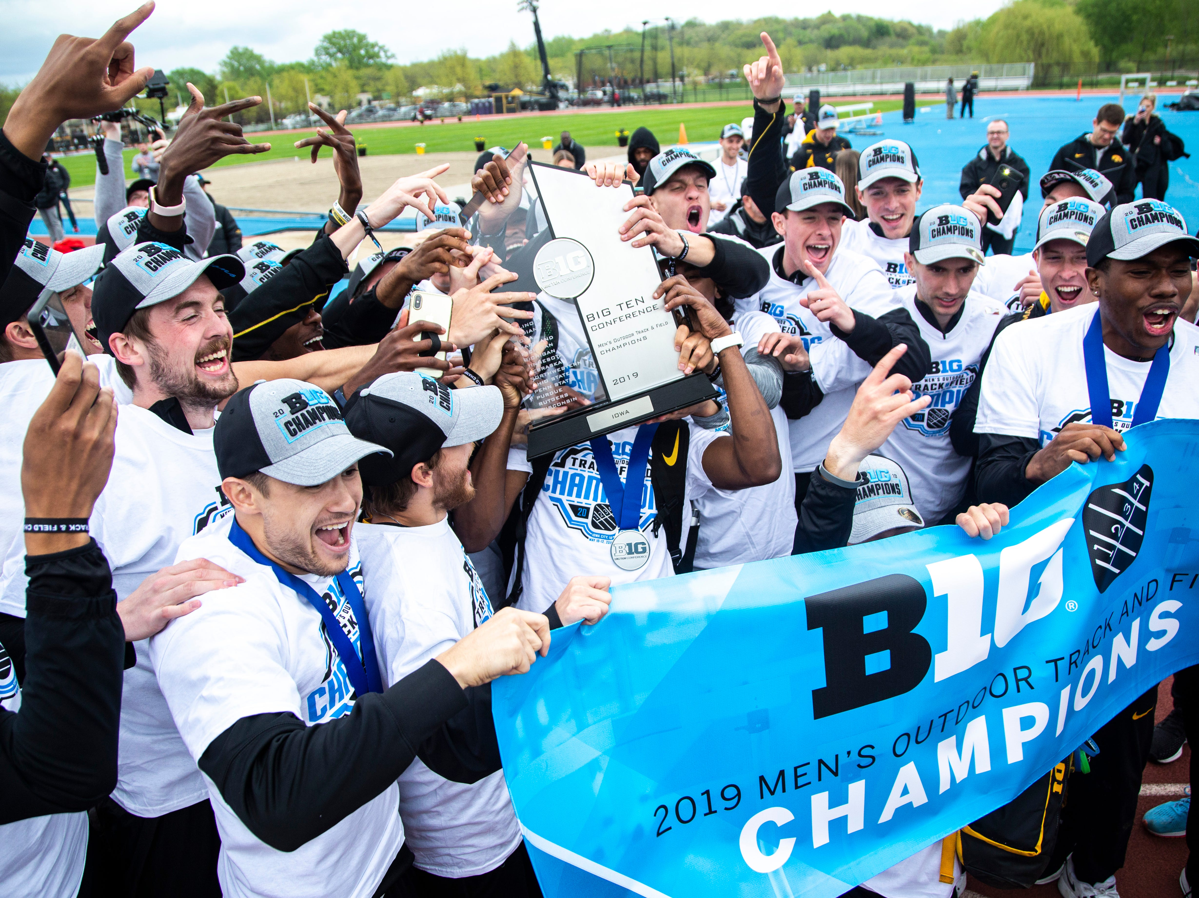 Iowa Hawkeyes men celebrate with the Big Ten Championship during the final day of Big Ten track and field outdoor championships, Sunday, May 12, 2019, at Francis X. Cretzmeyer Track on the University of Iowa campus in Iowa City, Iowa.