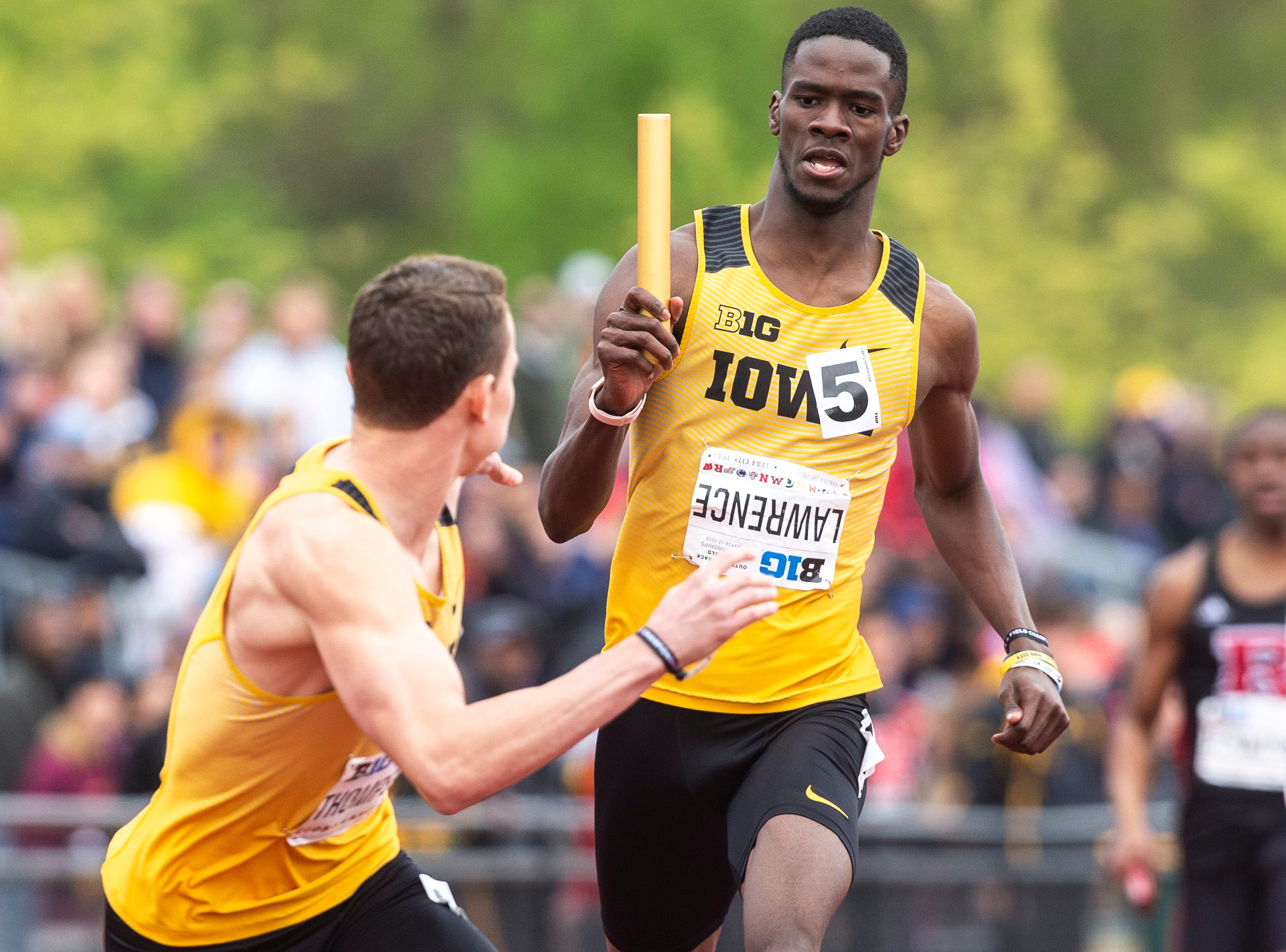 Iowa's Wayne Lawrence Jr. gives a handoff to teammate Chris Thompson, left, while they compete in the 4x400 meter relay during the final day of Big Ten track and field outdoor championships, Sunday, May 12, 2019, at Francis X. Cretzmeyer Track on the University of Iowa campus in Iowa City, Iowa. The Hawkeyes won, with a time of 3:07.36.