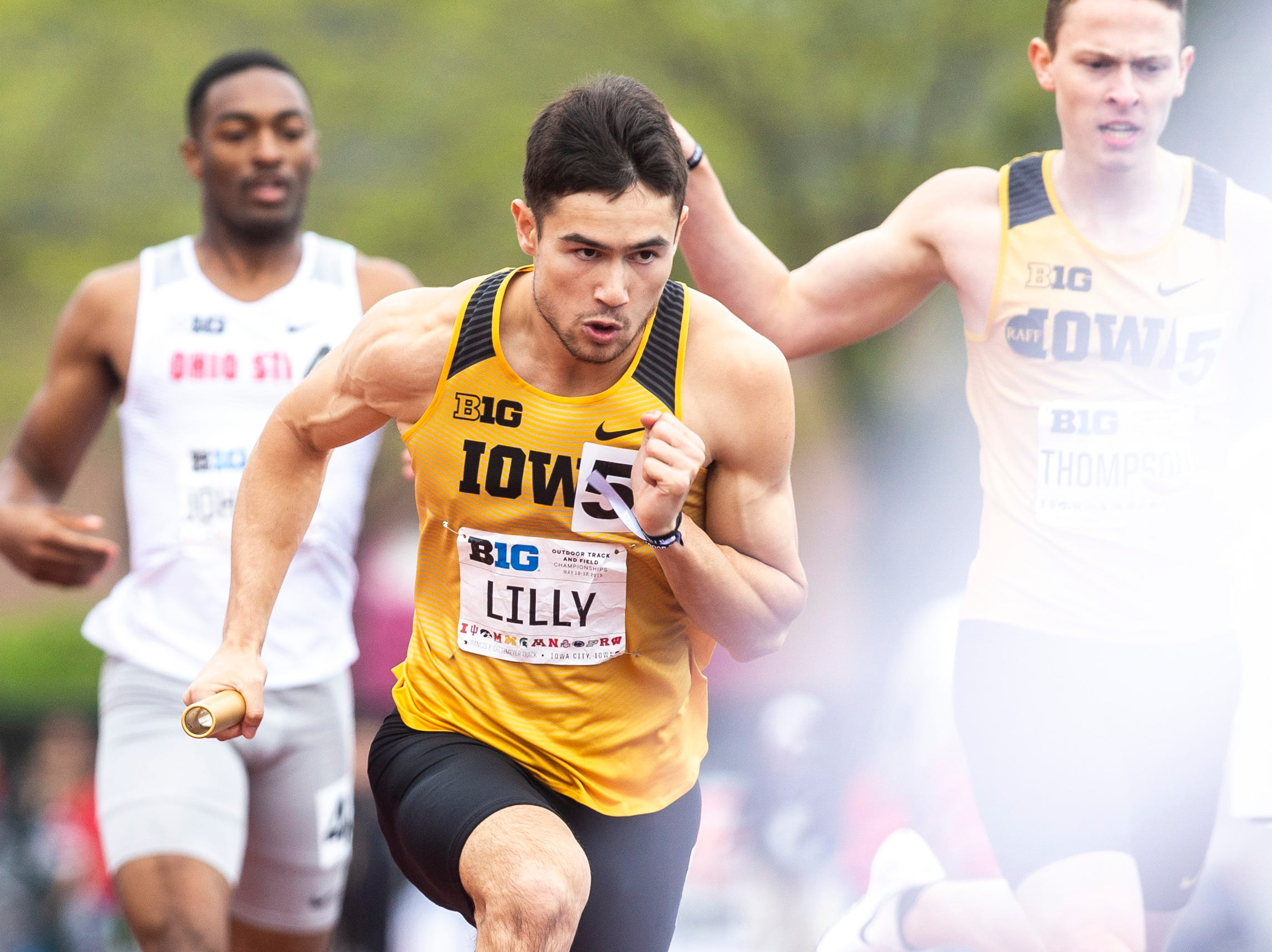 Iowa's Carter Lilly takes a handoff while competing in the 4x400 meter relay during the final day of Big Ten track and field outdoor championships, Sunday, May 12, 2019, at Francis X. Cretzmeyer Track on the University of Iowa campus in Iowa City, Iowa. The Hawkeyes won, with a time of 3:07.36.