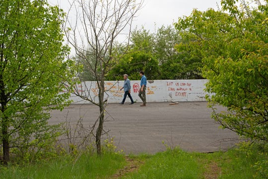Mario Andretti  and IndyStar reporter Jim Ayello walk past graffiti at the defunct Nazareth Speedway.