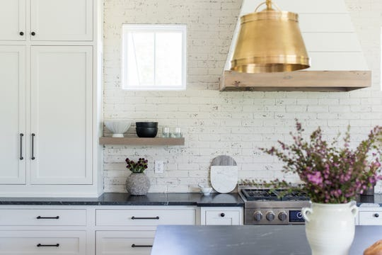 A shiplap exhaust fan sits against a whitewashed brick wall, over a stove flanked by open shelves and small windows.