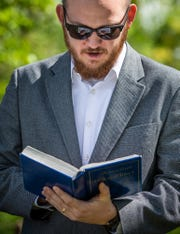Jesse Purvis, son of Jeff Purvis, reads an excerpt from the Bible during a small ceremony for Price Joyce, a former slaved owned by Purvis' great-great-great-grandfather, Alexander Joyce, on Saturday, May 11, 2019.