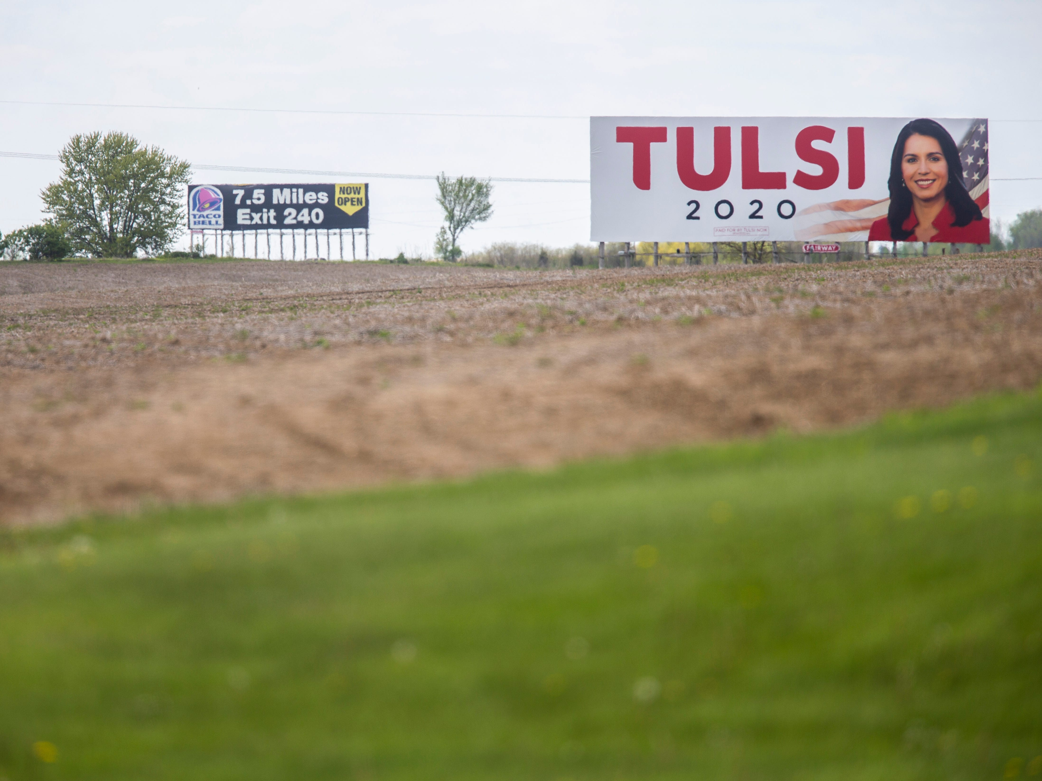 """A billboard with a photo of U.S. Rep. Tulsi Gabbard, D-Hawaii, and large red lettering reading """"Tulsi"""" with blue """"2020"""" below it is pictured, Monday, May 13, 2019, along Interstate 80 past Herbert Hoover Highway near Iowa City, Iowa. The ad says it was paid for by Tulsi Now, Gabbard's presidential campaign committee."""