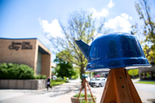 A blue tea pot attached to the top of a planter is pictured, Monday, May 13, 2019, in a community planter at City Hall along Washington Street in Iowa City, Iowa.