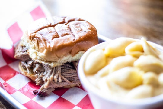 A pulled pork sandwich is pictured with a side dish of macaroni and cheese, Monday, April 8, 2019, at Pop's Old N' New Bar-B-Q in Iowa City, Iowa.