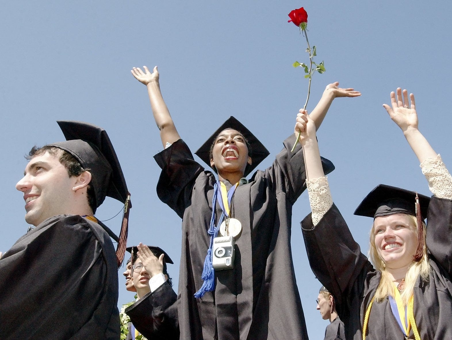 2003: Ithaca College graduates Michael Hemmenway, left, Ronica Reddick and Laurel Beversdorf wave to their parents in thanks for supporting them through college Sunday at the end of commencement ceremonies at Butterfield Stadium. Degrees were conferred onto 1,350 graduates at the annual commencement exercise.