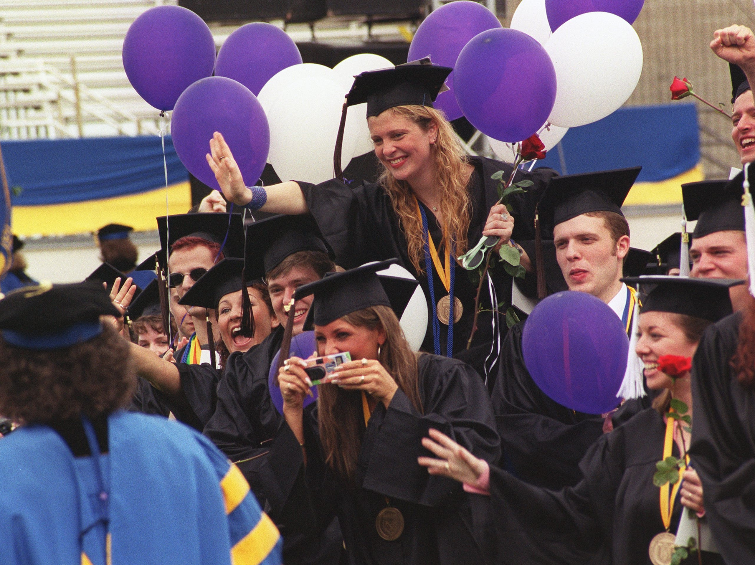 2000: Ithaca College graduates wave to Henry Winkler and IC President Peggy Williams as they walk up the aisle to the speakers' platform Saturday during commencement ceremonies.