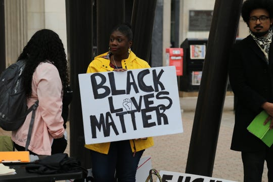 A protester holds a Black Lives Matter sign during a protest at the Bernie Milton Pavilion on the Ithaca Commons.