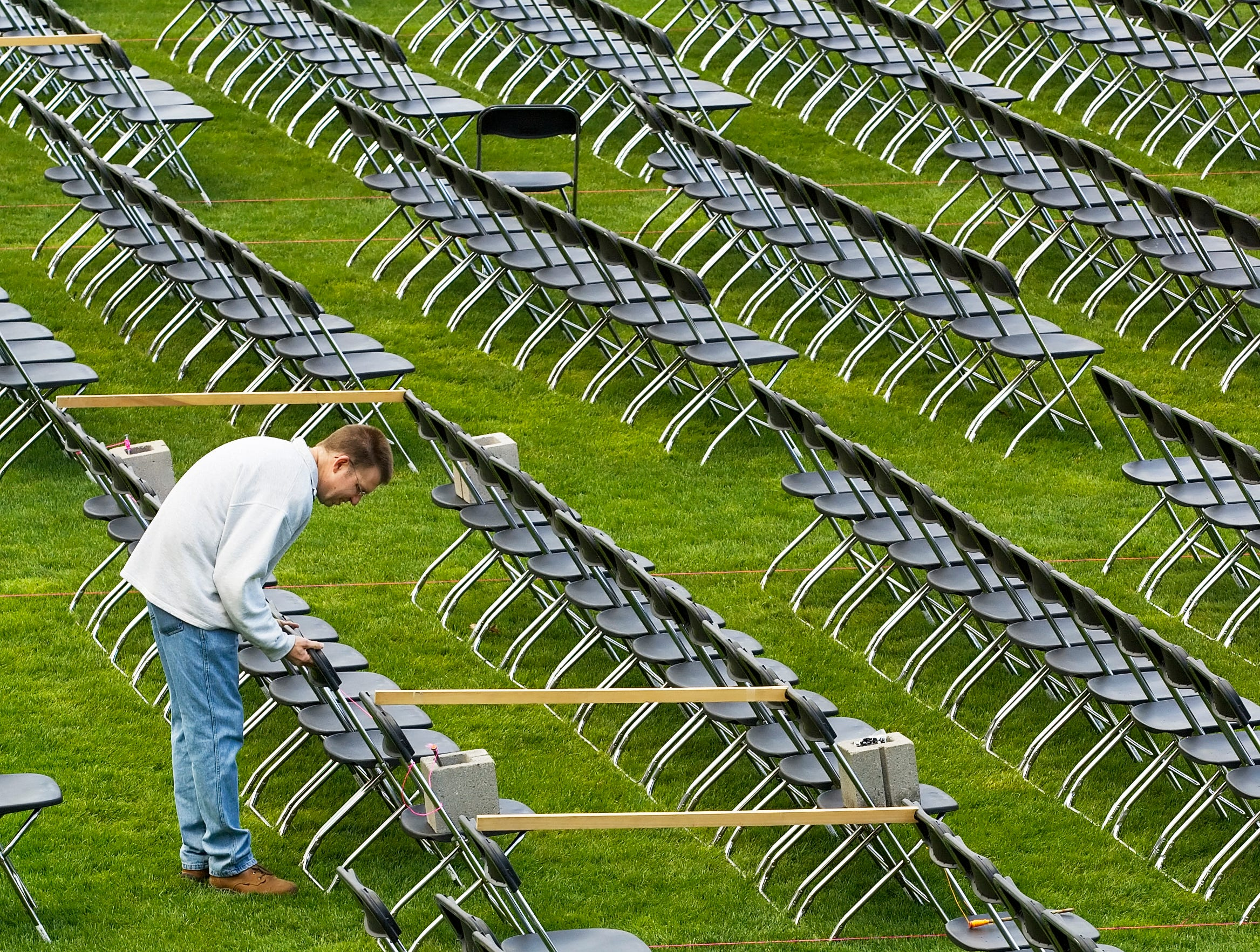 2007: Patrick Kelley and Ithaca College facilities attendant aligns the chairs on the field at Butterfield Stadium in preparation for graduation ceremonies to be held Sunday. The crew has been working since Tuesday to get the chairs out. Counting the bleachers there will be seating for 6942 people.