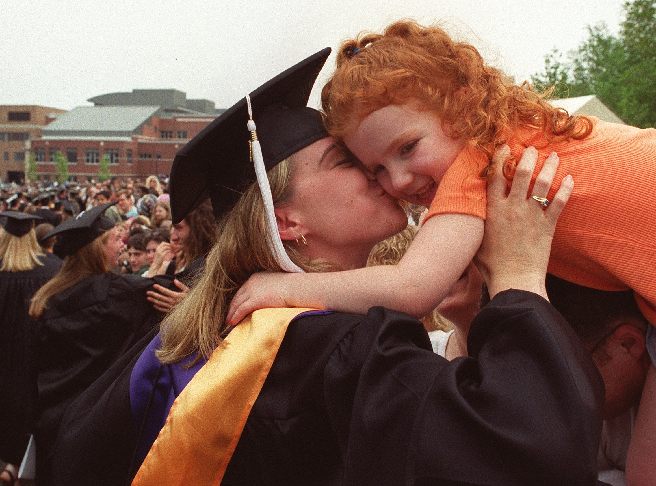 2000: Ithaca College graduate Amanda Parsons, left, gives Abigail Nickles a kiss at the end of commencement ceremonies Saturday. Parsons baby-sat for Nickles from the time she was an infant.
