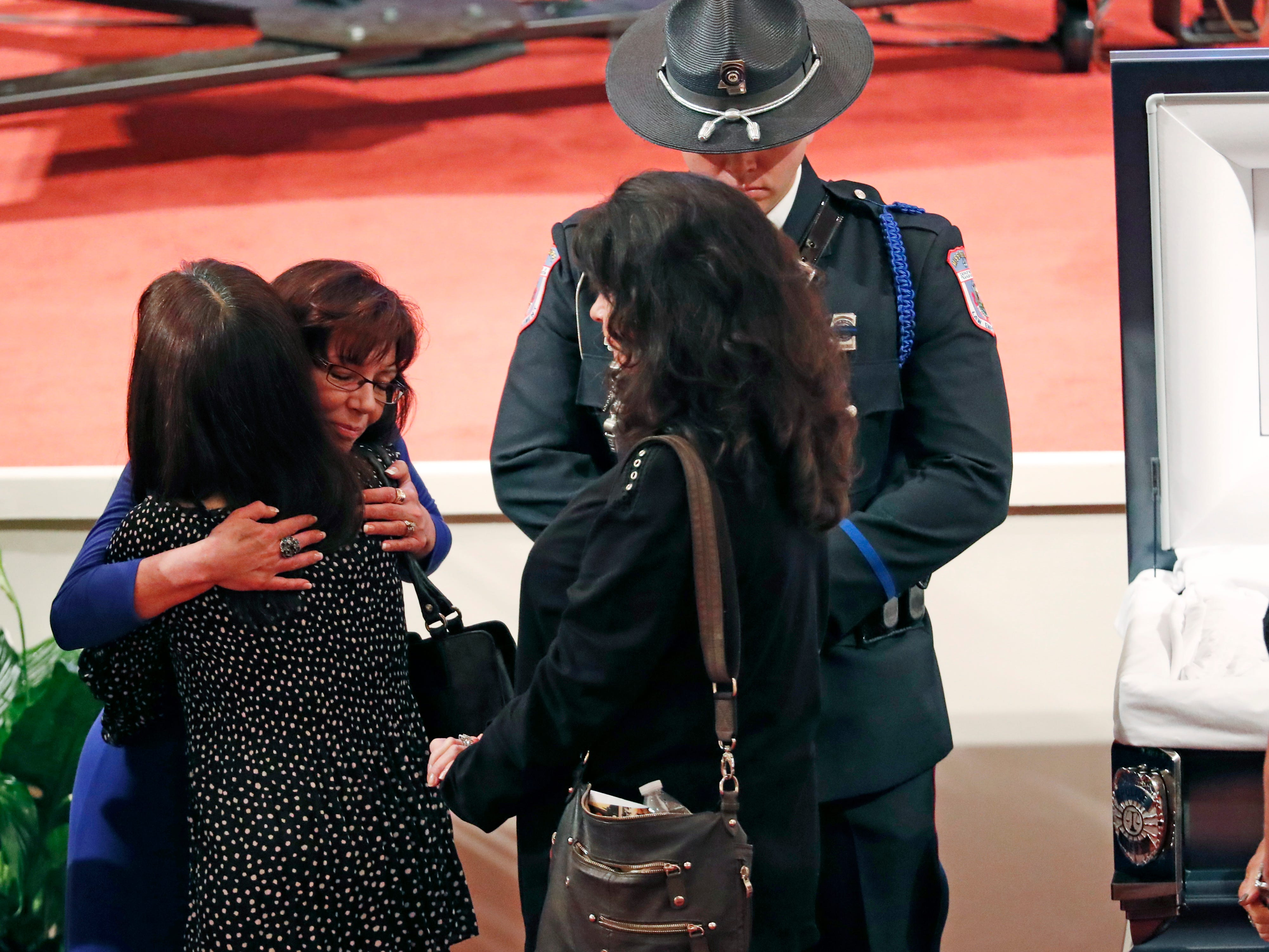 Pamela McKeithen, widow of officer Robert S. McKeithen, second from left, hugs a mourner as a member of a law enforcement agency honor guard, stands watch, as people pay their respects to McKeithen and his family in the First Baptist Church of Biloxi, Monday morning, May 13, 2019, prior to the funeral service.