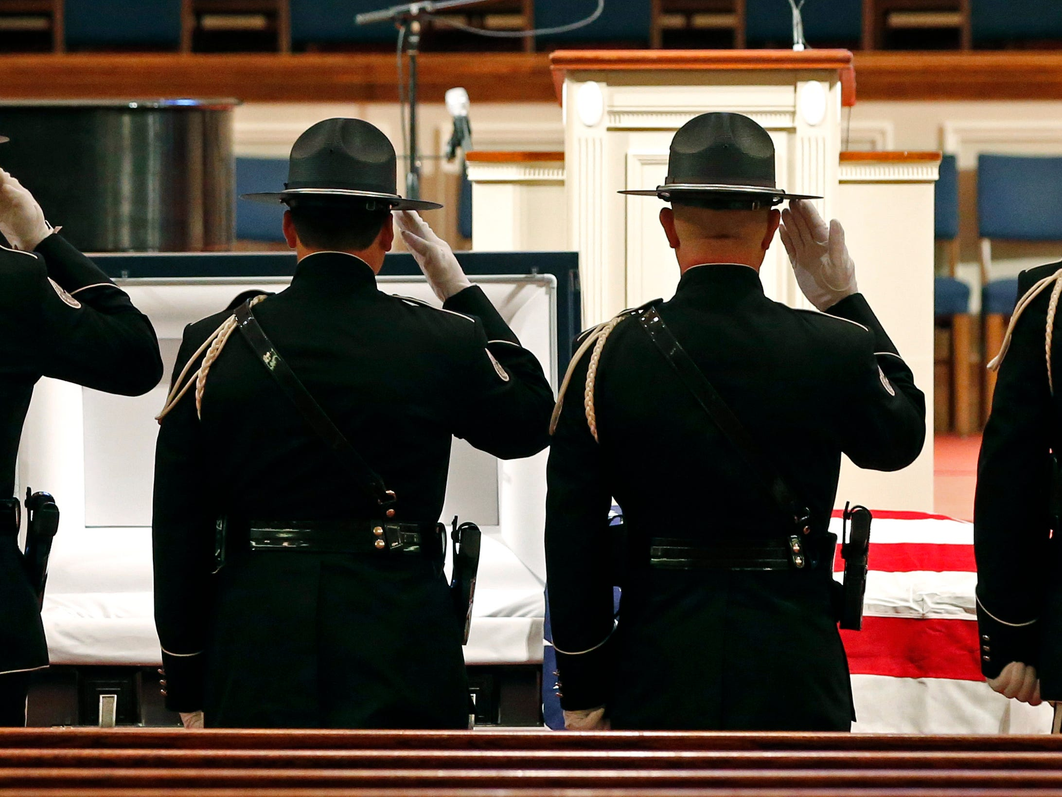 Members of the Biloxi Police Department Honor Guard salute the body of officer Robert McKeithen after escorting him into the First Baptist Church of Biloxi, Miss., Monday, May 13, 2019, prior to visitation. McKeithen was killed outside Biloxi's police station May 5.