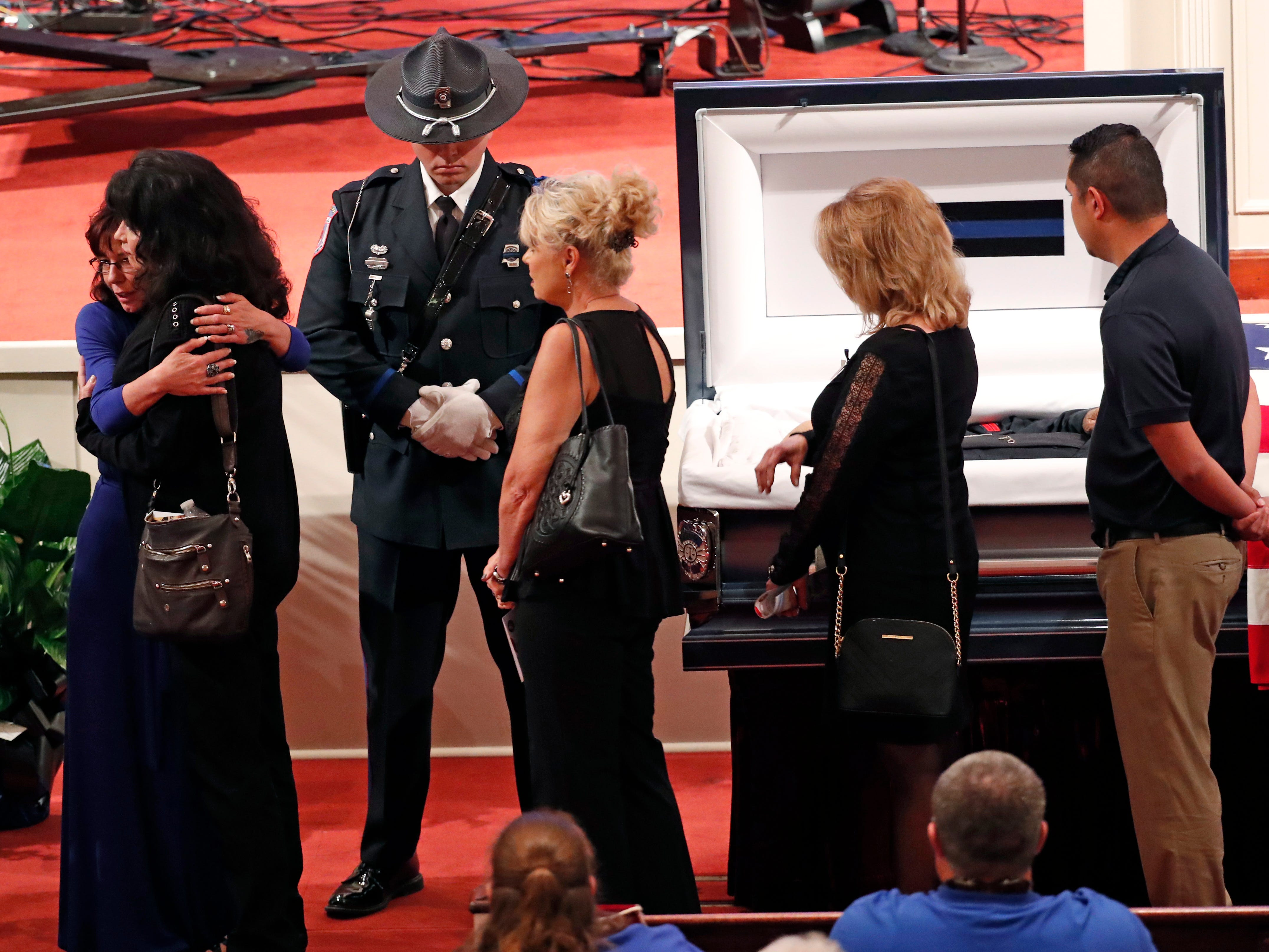 Pamela McKeithen, widow of officer Robert S. McKeithen, left, hugs a mourner as visiting law enforcement officers, friends and community residents pay their last respects to McKeithen and his family in the First Baptist Church of Biloxi, Monday morning, May 13, 2019, prior to the funeral service.