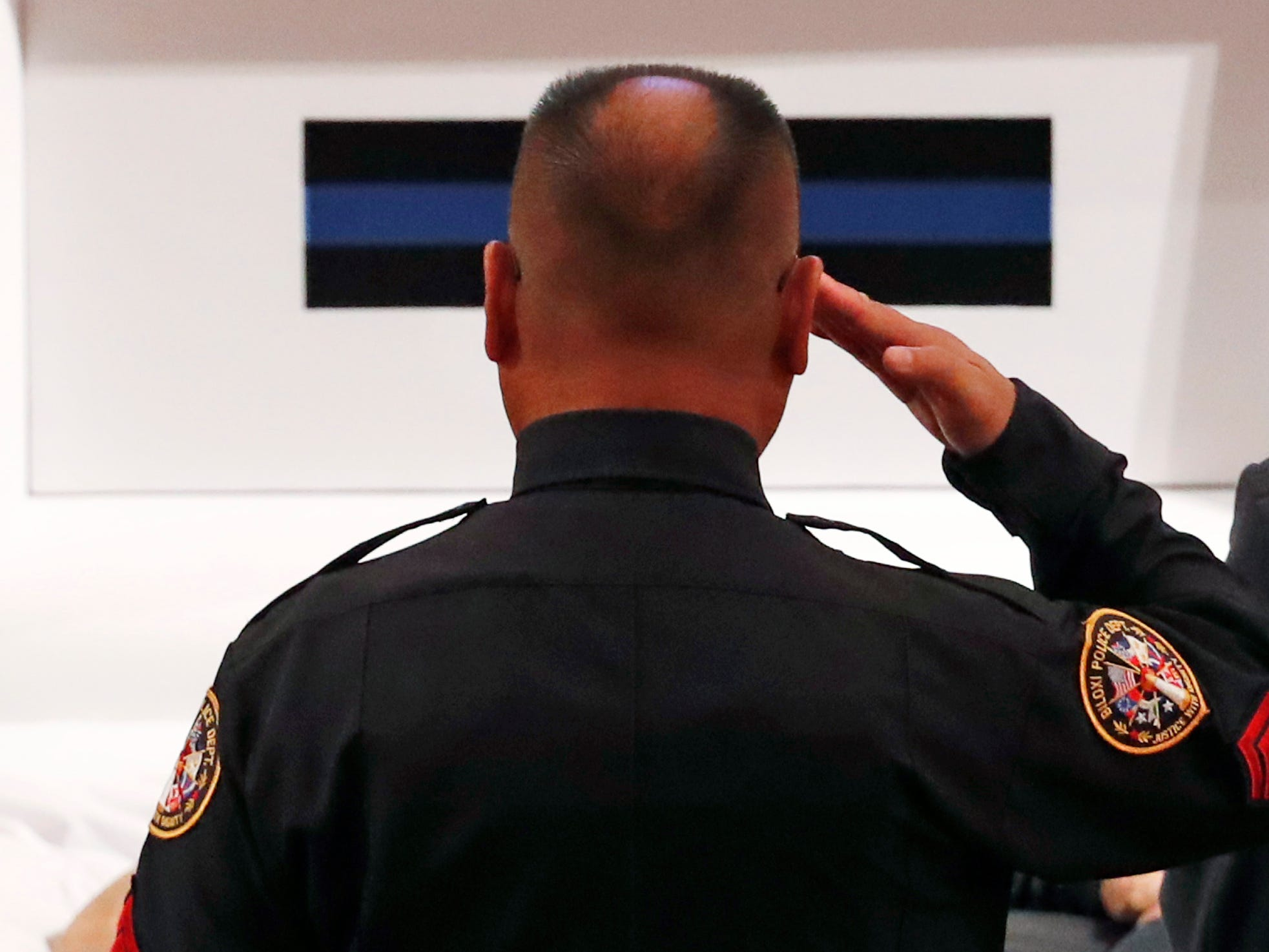 A lone policeman salutes the body of officer Robert S. McKeithen, during visitation at the First Baptist Church of Biloxi, Miss., Monday morning, May 13, 2019. McKeithen was killed outside headquarters May 5.