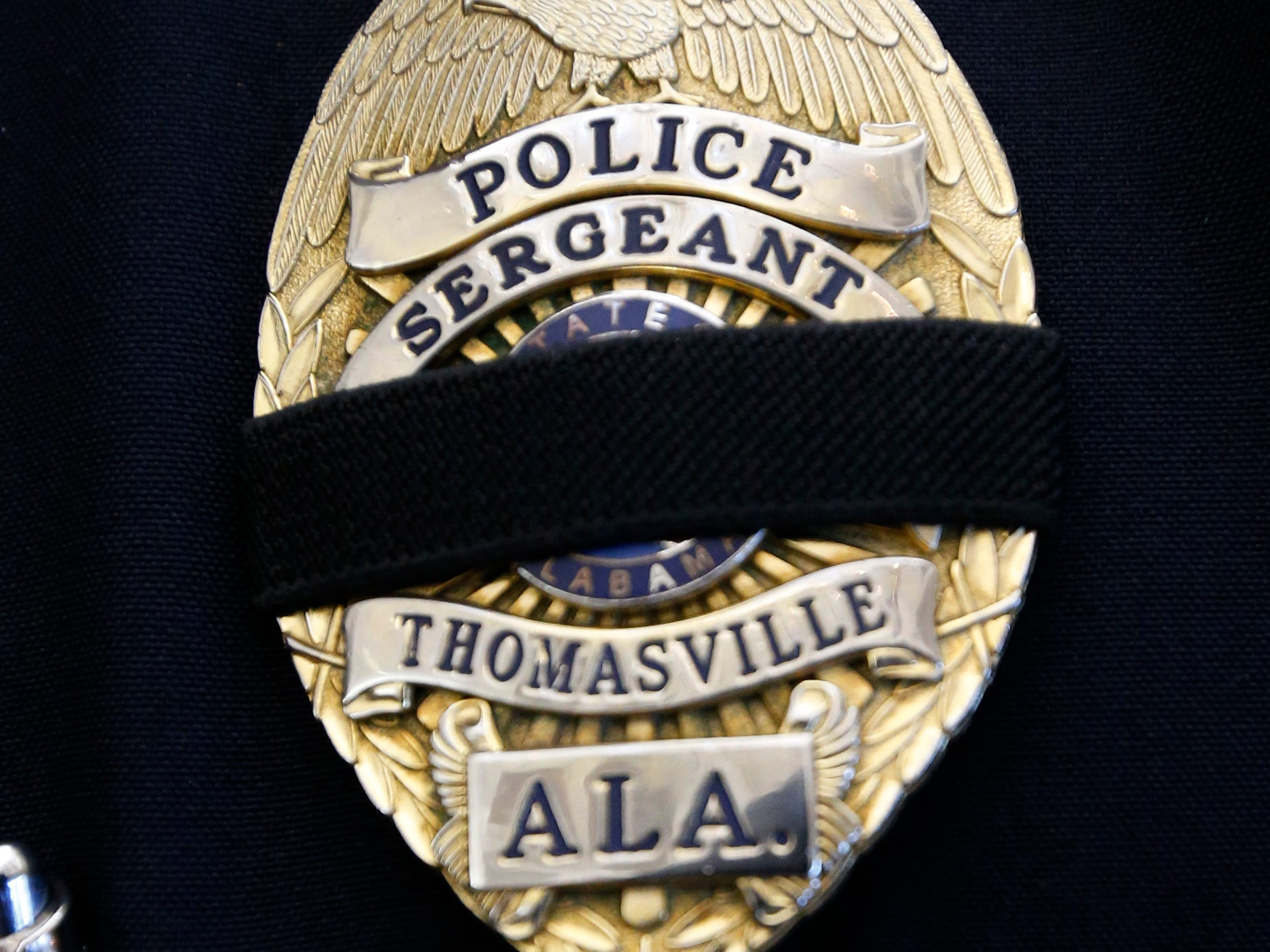 Visiting law enforcement officers, such as Lt. Rusty Hardeman, unseen, of the Mobile, Ala., Police Department, wear a black band on his badge as acknowledgment of a fallen officer such as the case of Biloxi, Miss., police officer Robert S. McKeithen, at his funeral service at the First Baptist Church of Biloxi, Monday, May 13, 2019.