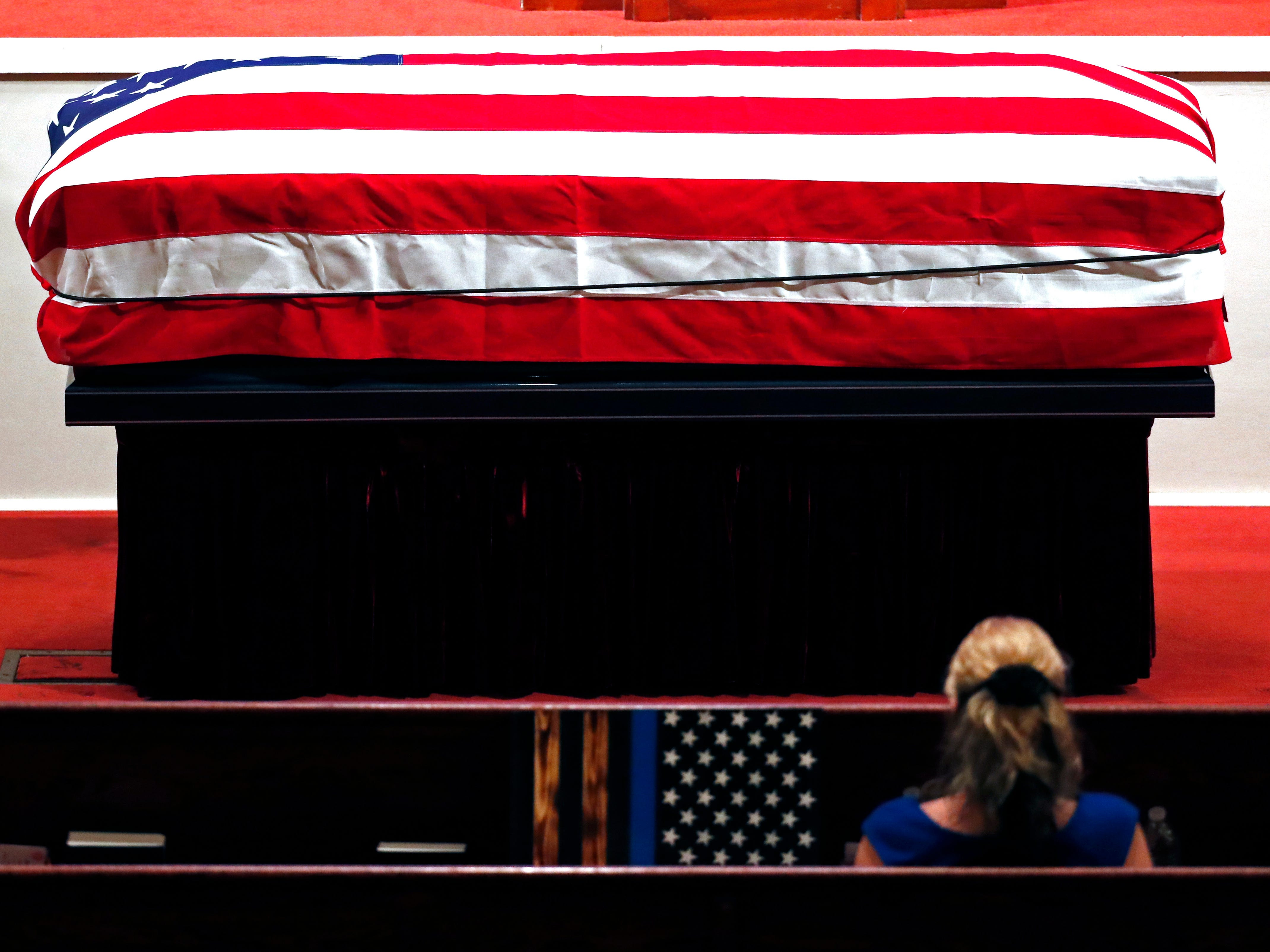 A friend of the family sits across the casket of Biloxi police officer Robert S. McKeithen, while waiting for the funeral service to start at the First Baptist Church of Biloxi, Miss., Monday, May 13, 2019.