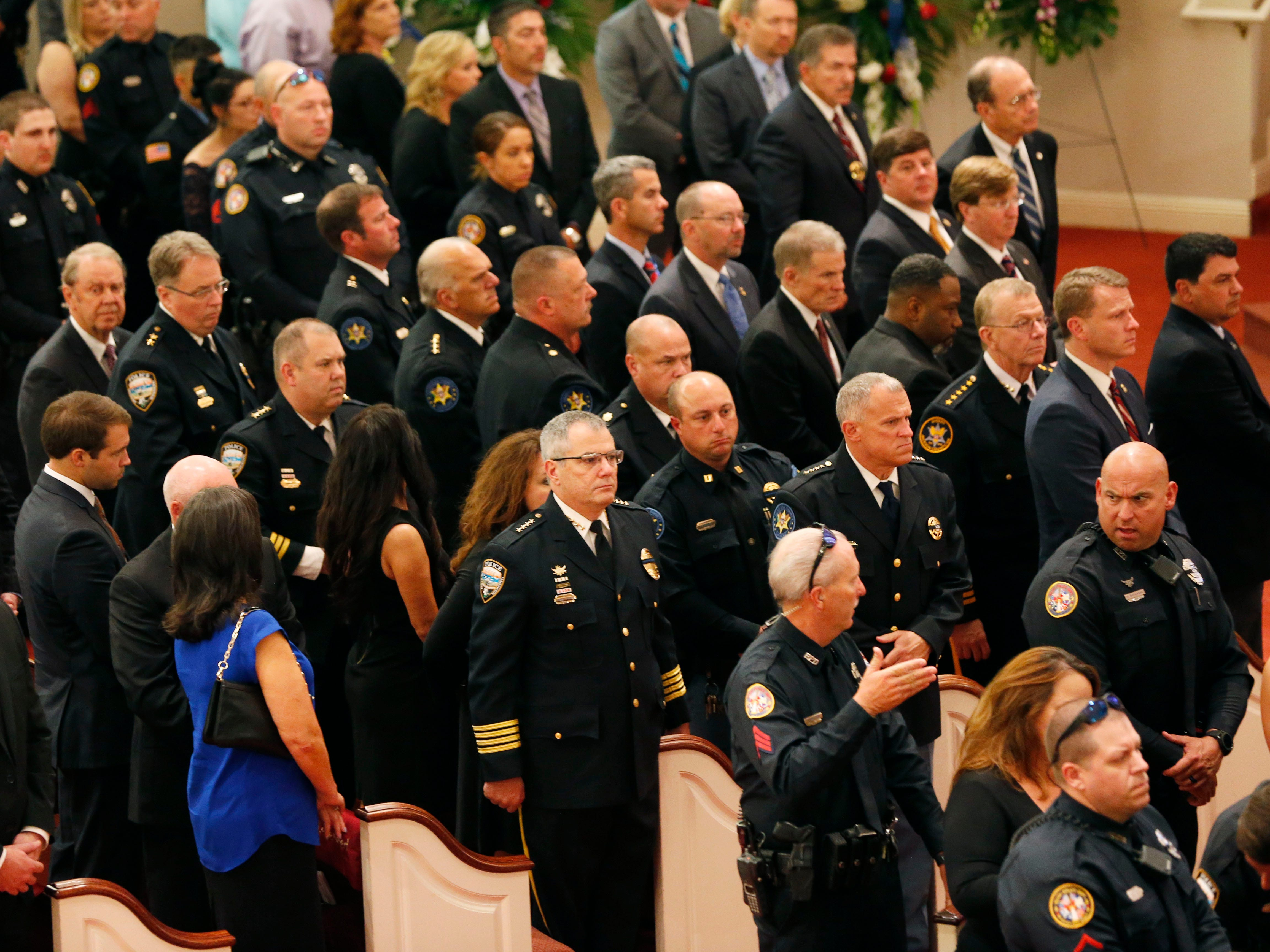 Visiting law enforcement officers, friends and community residents, stand to pay their last respects to officer Robert S. McKeithen and his family as they exit the First Baptist Church of Biloxi, Monday, May 13, 2019, following funeral services.