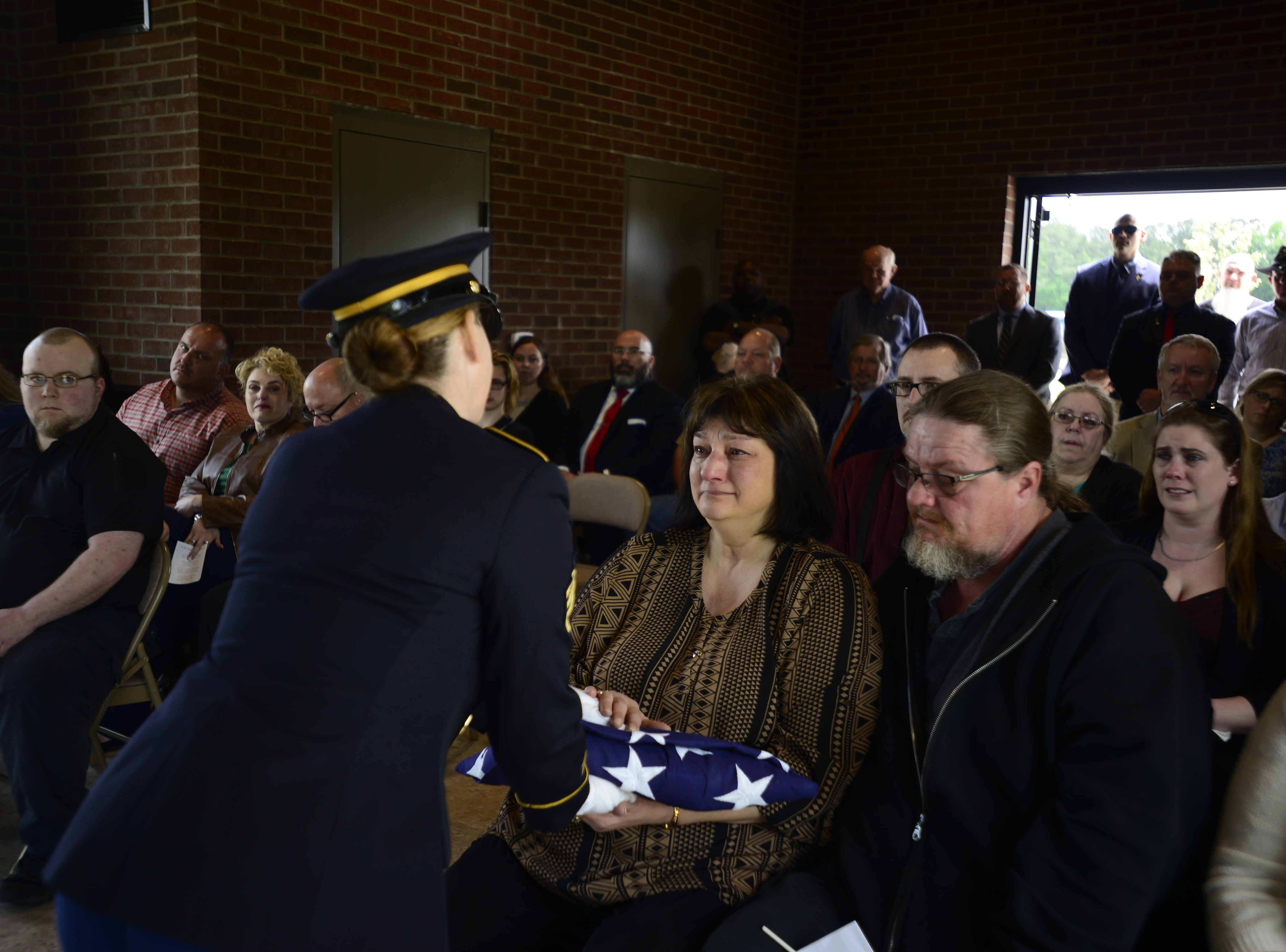 A soldier presents a flag to one of Robert Martin's sisters during his funeral service.