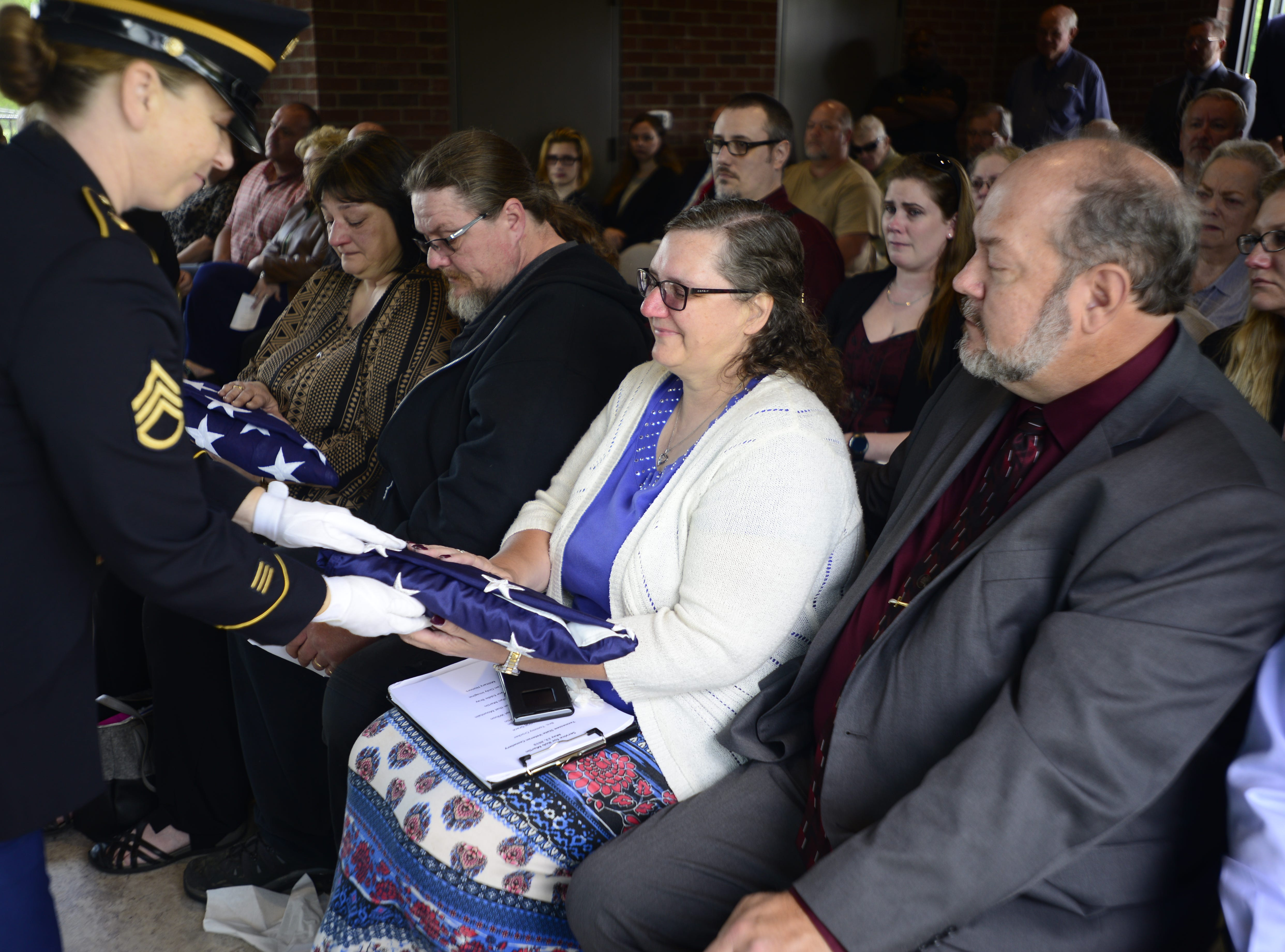 A soldier who stood around the remains of Robert Martin presents his sister Colleen Hardee with a flag.
