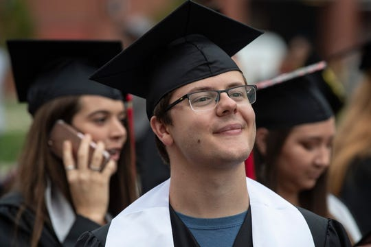 Louisville native Clay Harville, left, walks with fellow graduates during the Topper Walk at Western Kentucky University. Harville is the first to graduate from WKU's autism program with a degree in special education teaching.