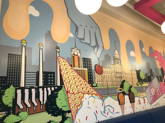 A colorful mural inside the new Baskin Robbins store in East Lansing features local landmarks, including the State Capitol and  the Eckert Power Plant with its triple smokestacks.