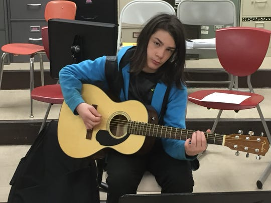 Kent Kuhn plays guitar Monday morning at Shelby Middle School.
