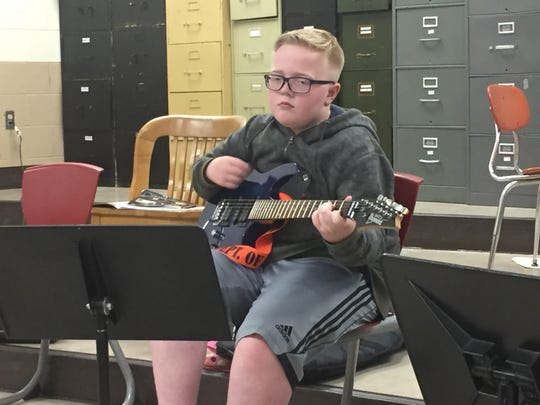 Tristan Jones strums his electric guitar.
